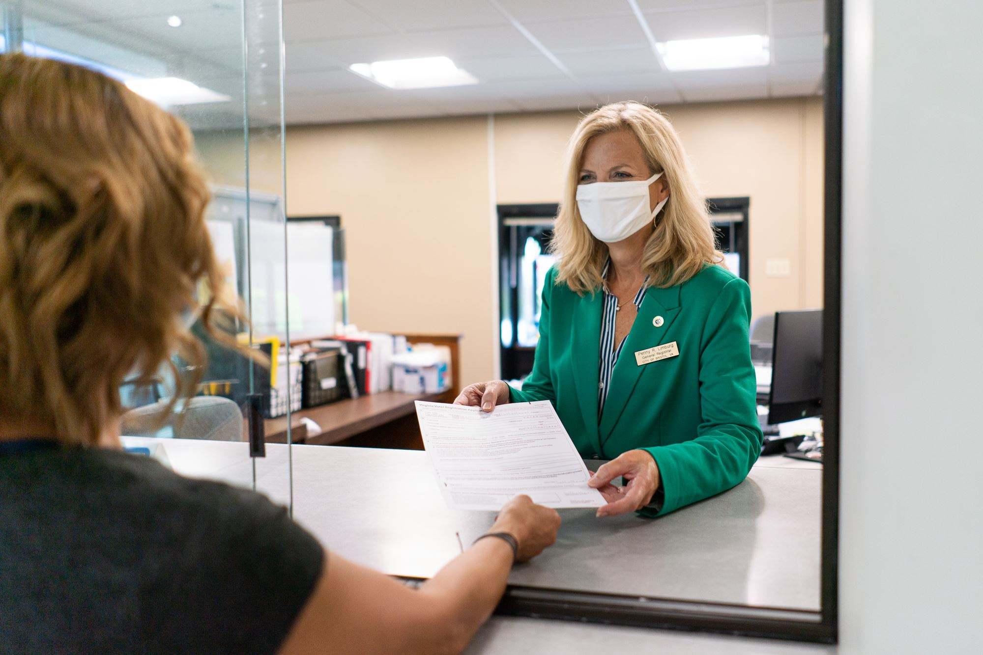 Employee handing voter registration form to citizen wearing masks